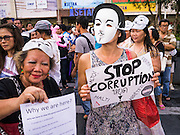 "09 JUNE 2013 - BANGKOK, THAILAND:  Members of the White Mask protest movement at an anti-government protest on the plaza in front of Central World in Bangkok. The White Mask protesters wear the Guy Fawkes mask popularized by the movie ""V for Vendetta"" and the protest groups Anonymous and Occupy. Several hundred members of the White Mask movement gathered on the plaza in front of Central World, a large shopping complex at the Ratchaprasong Intersection in Bangkok, to protest against the government of Thai Prime Minister Yingluck Shinawatra. They say that her government is corrupt and is a ""puppet"" of ousted (and exiled) former PM Thaksin Shinawatra. Thaksin is Yingluck's brother. She was elected in 2011 when her brother endorsed her.    PHOTO BY JACK KURTZ"