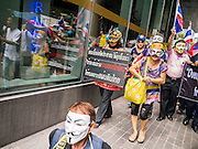 """02 JUNE 2013 - BANGKOK, THAILAND:   A legless man (lower center) leads a protest march through the Bangkok skywalk system. About 300 people wearing the Guy Fawkes mask popularized by the movie """"V for Vendetta"""" and Anonymous, the hackers' group, marched through central Bangkok Sunday demanding the resignation of Prime Minister Yingluck Shinawatra. They claim that Yingluck is acting as a puppet for her brother, former Prime Minister Thaksin Shinawatra, who was deposed by a military coup in 2006 and now lives in exile in Dubai.   PHOTO BY JACK KURTZ"""