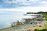 Low tide reveals a rocky stretch of beach in a small cove within Chiniak Bay on Kodiak Island in Southwestern Alaska. Summer. Morning.