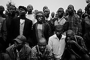 """NAIROBI, KENYA - AUGUST 28, 2011: A crowd of Luo youth listen to exhortations from a community leader in Kisumundogo village during a weekly """"kamkunji"""" gathering. During the post-election violence of 2007 and 2008, many Kenyan youth were killed while carrying out acts of violence on behalf of corrupt Ministers of Parliament. """"They have realized that they were used by other people,"""" one Kenyan explained about the youth, """"so they've promised to never to do that again. They are the ones who preach peace, because they were most affected.""""<br /> <br /> Various grassroots initiatives led by youth have begun to improve the quality of life for those living in the direst of conditions, and young people of different tribes are using gardening, waste removal, education and athletics to encourage their peers toward a self-respecting and self-sustaining community. Termed """"youth groups"""" on the street, these initiatives could represent the future of long-term socioeconomic development in Kenya while laying the groundwork for a more peaceful election in 2013. During the post-election violence of 2007 and 2008, impoverished youth in Kenya were routinely bribed by the nation's political elite to carry out acts of violence in their communities. Idleness among the youth, combined with the nation's history of tribal rivalries, were cited as a key factors to the violence, culminating in the deaths of over 1,200 Kenyans and the displacement of over 600,000. Since the violence, many youth have begun to seize active roles in the reform of their nation. In 2010 United States Ambassador Michael Ranneberger said he sensed """"a sea change of attitude"""" among youths, """"a tidal wave below the surface. The youth have woken up."""""""