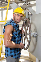 Portrait of confident young worker fixing industrial valve