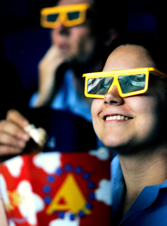 Alcante. Cinemas Abaco, a girl eating pop corns.  wearing 3D glasses © Vicens Gimenez