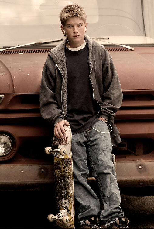 Skateboarder standing by old truck.