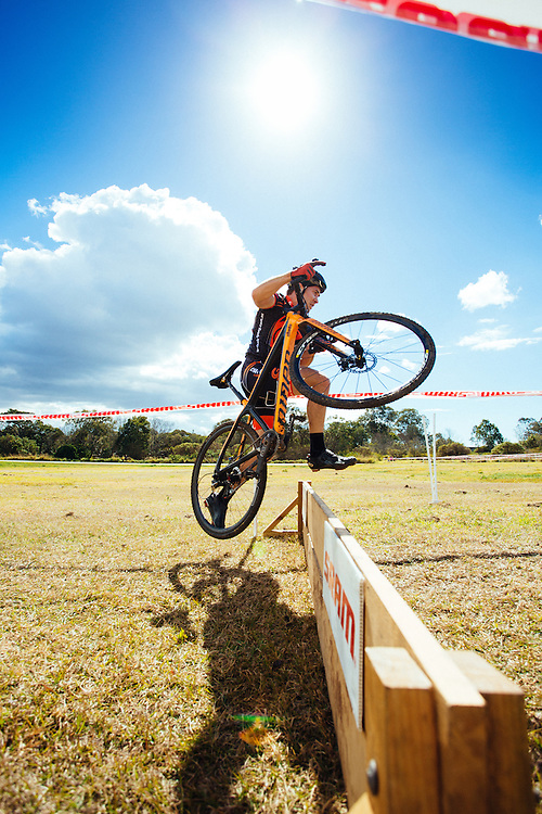 A cyclocross rider lifts and jumps with his bike over a barrier in a local cyclocross race.