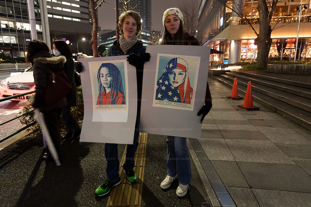 A younger man and woman hold painting to illustrate  the multi-cultural aspect of the United States during a protest march by members of the Democratic Party Abroad organisation to mark the inauguration of President Donald Trump, Tokyo, Japan. Friday January 20th 2017 Around 400 people took apart in the march, which started in Hibiya Park at 6:30pm and finished in Roppongi just before 8pm, to honour the service given by President Obama and to protest against the illiberal policies expected of the new administration of President  Trump.