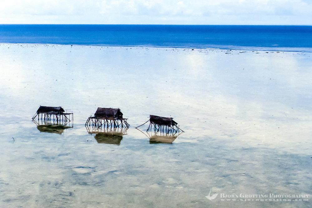 Maluku, North Maluku, Halmahera. Small bamboo shelters on a beach close to Halmahera (from helicopter)