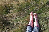 Person wearing pink galoshes lying in grass low section