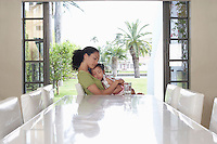 Mother and daughter (5-6 years) embracing sitting at dining table