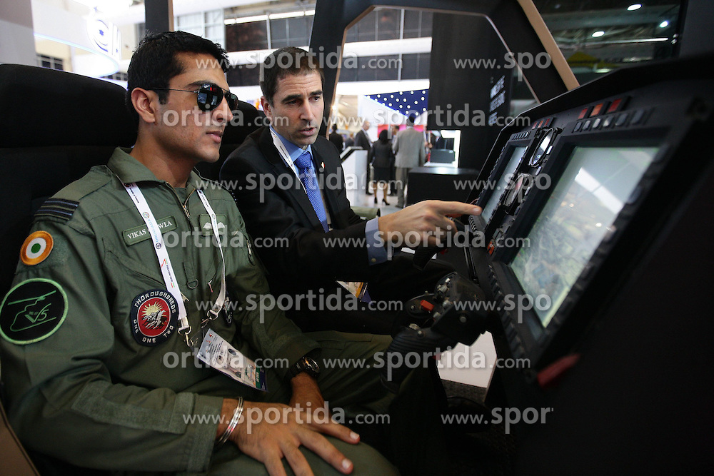 An Israeli exhibitor shows an Indian pilot a weapon control system at the Aero India 2015 in Air Force Station Yelahanka of Bangalore, India, Feb. 18, 2015. The biennial air show this year attracted dealers from 49 countries, showcasing their aero-related products in military and civilian fields. EXPA Pictures © 2015, PhotoCredit: EXPA/ Photoshot/ Zheng Huansong<br /> <br /> *****ATTENTION - for AUT, SLO, CRO, SRB, BIH, MAZ only*****