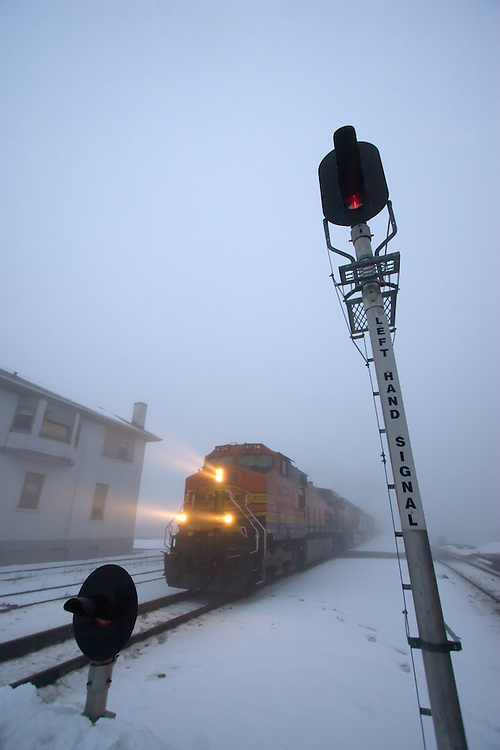 Appearing out of a thick bank of fog, an eastbound BNSF intermodal train pounds across the diamonds at Joliet Union Depot.