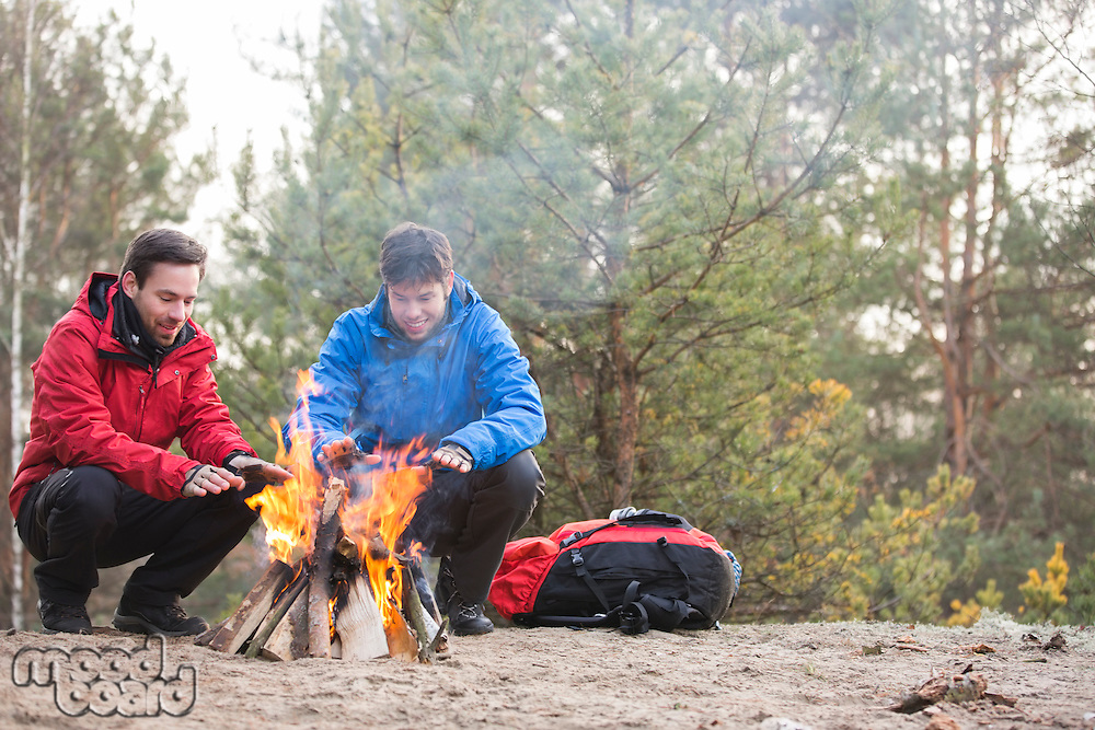 Male backpackers warming hands at campfire in forest