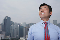 Portrait of young business man office buildings in background