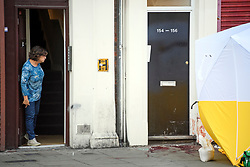 © Licensed to London News Pictures. 13/09/2019. London, UK. A resident looks at large patched of blood in a doorway at the scene on Camden HIgh Street in North London where a man was last night stabbed to death and another man remains in hospital with a knife wound. Photo credit: Ben Cawthra/LNP