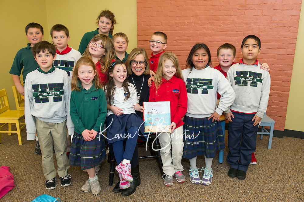 "Author Elizabeth Howard sits with Mrs. Gressner's 2nd and 3rd grade students from Holy Trinity School after reading them ""A Day with Bonefish Joe"" at the Laconia Library Tuesday afternoon.  (Karen Bobotas/for the Laconia Daily Sun)"