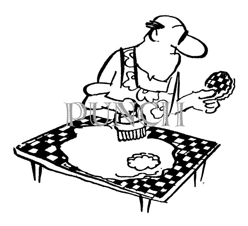 (A man using a pastry cutter cuts out a piece of of the table top as well as the pastry)