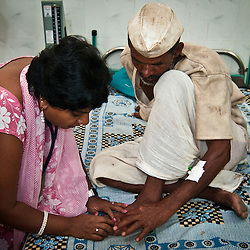 A snake bite victim has his bite inspected.  When treated quickly most of India's snake bite victims can be cured.