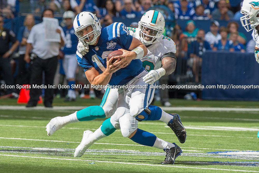September 15, 2013: Indianapolis Colts quarterback Andrew Luck (12) is pulled down by Miami Dolphins linebacker Dannell Ellerbe (59) during the football game between the Indianapolis Colts vs Miami Dolphins at Lucas Oil Stadium in Indianapolis, IN.