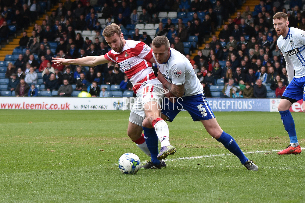 Doncaster Rovers Forward,  Andy Williams  and Bury Defender, Peter Clarke tussle during the Sky Bet League 1 match between Bury and Doncaster Rovers at the JD Stadium, Bury, England on 9 April 2016. Photo by Mark Pollitt.