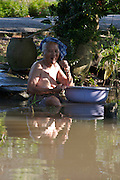 Mekong Delta. Old lady having a morning wash in the river.