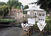 Belgie, Brugge, 3-9-2005..Een schilder van stadsgezichten begint aan een nieuw doek terwijl toeristen zich in een rondvaartboot door de oude binnenstad laten varen. Architectuur, monumenten, stadsgezicht..Belgium, stedentrip, toerisme, tourism. Vakantie...Foto: Flip Franssen/Hollandse Hoogte
