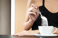 Woman pouring sugar into tea cup mid section close up