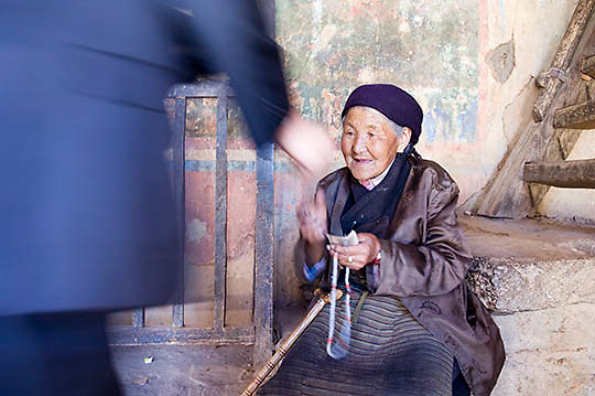 Elderly Tibetan Lady with cane resting on steps outside Temple. Lhasa, Tibet. Asia.