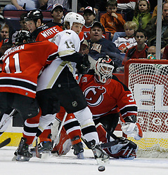 Mar 14, 2007; East Rutherford, NJ, USA;  Pittsburgh Penguins left wing Ryan Malone (12) battles in front of the net after a New Jersey Devils goalie Martin Brodeur (30) during the first period at Continental Airlines Arena in East Rutherford, NJ. Mandatory Credit: Ed Mulholland-US PRESSWIRE Copyright © 2007 Ed Mulholland