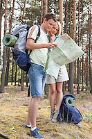 Full length of young hiking couple reading map in forest