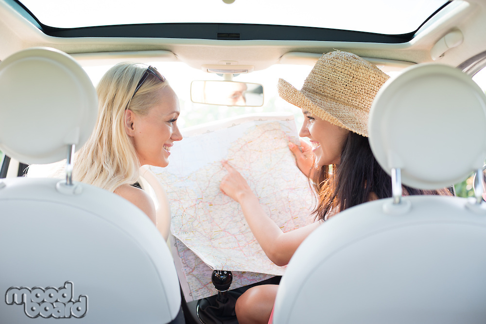Rear view of happy women reading map in car