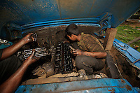 2005-10-24 Batticaloa, Sri Lanka. Boy working in an open air truck garage. His small size is good to reach difficult spots inside the engine compartment.