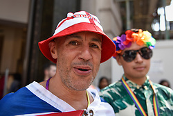 © Licensed to London News Pictures. 07/07/2018. LONDON, UK. An England fan from Camden to watch the England v Sweden World Cup football match views the annual Pride in London Parade, the largest celebration of the LGBT+ community in the UK.  Photo credit: Stephen Chung/LNP