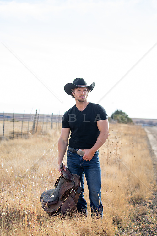 cowboy holding a saddle in a field