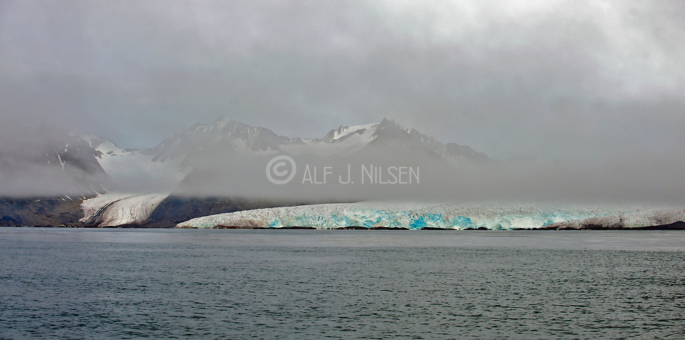Foggy mountains and glacier on the western coast of Spitsbergen, Svalbard in early August 2012.