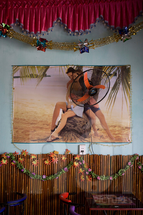 A poster of a couple on a dreamy beach hangs on the wall of a cafe with a fan attached in the center of the image, Vietnam, Southeast Asia.