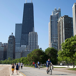Photo of Chicago Lakefront Trail with people walking, biking, and jogging with the Hancock Building and Chicago skyline. Photo is vertical, high resolution, and was taken in may 2010.