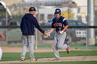 KELOWNA, BC - JULY 17:  Trent Sellers #7 of the Wenatchee Applesox gets a low five from the coach as he rounds third base for home against the Kelowna Falcons at Elks Stadium on July 17, 2019 in Kelowna, Canada. (Photo by Marissa Baecker/Shoot the Breeze)
