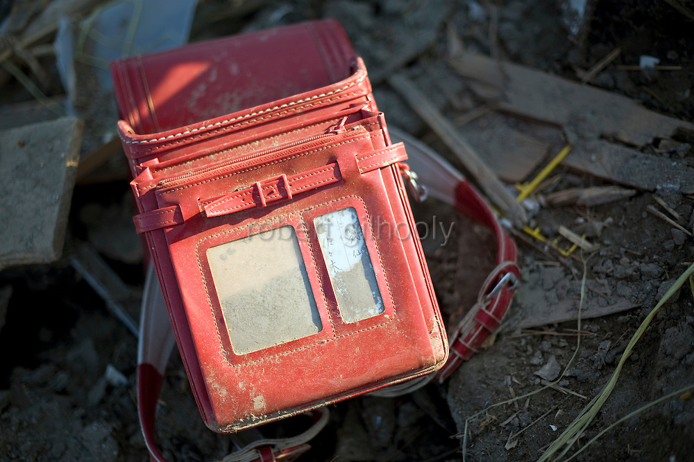 An primary school student's bag lies in the rubble of  Rikuzentakata, Iwate Prefecture, Japan on 06 April, 2011. .Photographer: Robert Gilhooly