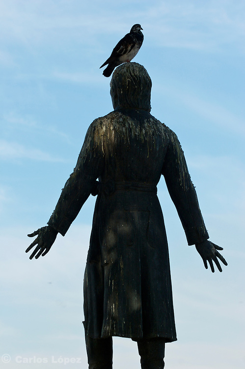"A dirty statue of the priest of ""dolores"" ( cura de dolores ), Don Miguel Hidalgo y Costilla with a pigeon on top of his head in the city of Manzanillo of the state of Colima in Mexico."
