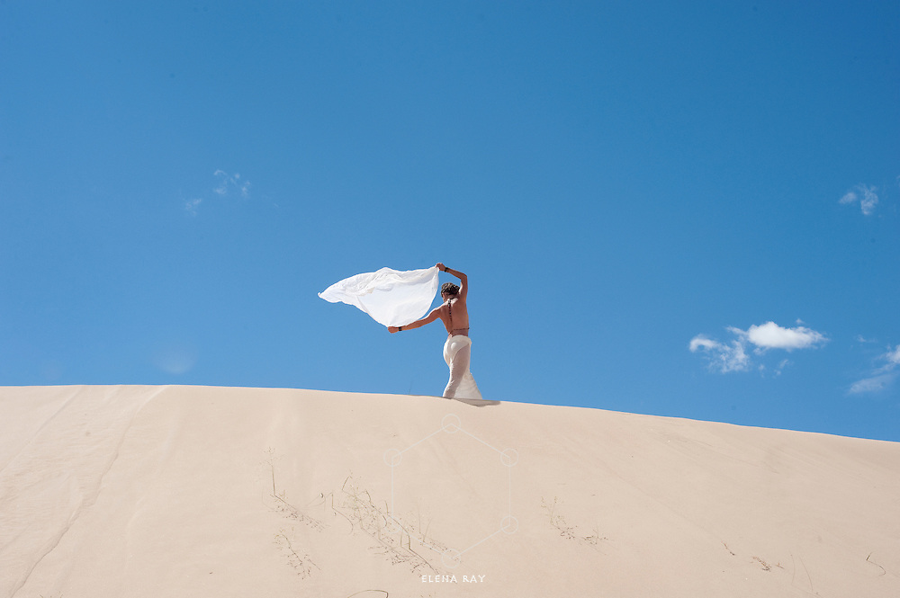 A woman high on a dune with her white  scarf blowing in the breeze.<br /> :::<br /> :::<br /> &quot;The mind is like the wind and the body is like the sand; if you want to know how the wind is blowing, you can look at the sand.&quot;<br /> -Bonnie Bainbridge-Cohen:
