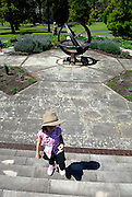 Child (6 years old) on steps in Royal Botanic Garden Herb Garden, with Sundial in background. Sydney, Australia