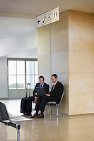 Two business men using laptop in airport lobby