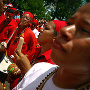 DANCING DEVILS OF YARE / LOS DIABLOS DE YARE<br /> Photography by Aaron Sosa<br /> Yare, Mirana State - Venezuela 2009.<br /> (Copyright © Aaron Sosa)<br /> <br /> The Dancing Devils of Yare is a religious festival held in the town of San Francisco de Yare in Miranda State, Venezuela.<br /> <br /> Every Corpus Christi, or 60 days after Easter, men from Yare dress in red robes, capes and masks of grotesque demons and dance in the streets to the rhythm of drumbeats and maracas. They adorn their costumes with scapulars, rosaries, crosses and other religious objects.<br /> <br /> After dancing the devils congregate at the historical San Francisco Catholic church and kneel in silence before being blessed by a priest. The kneeling symbolizes respect and their religious promise to end their evil ways. After being blessed, dancing and music continue as the devils go in a large procession to visit the homes of the deceased throughout their town. The celebration lasts until the end of the afternoon, when church bells are sounded and brotherhood spreads, signifying the triumph of good over evil for one more year.<br /> <br /> The festival's origins date back to the eighteenth century, and being allowed to participate is considered a tremendous honor. The fraternity of men associated with the festival is celebrated as the oldest brotherhood still practicing its traditions, on the entire American continent. Their masks differentiate their place in the fraternity's hierarchy, and it is not uncommon to find men who have danced annually as devils for more than twenty or thirty years.