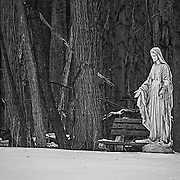 This image was shot in the first (blue) light of day.  I was struck by the warmth of the statue, the open welcoming arms, contrasted to the cold of the snow.  It almost appears that her right hand is pointing to the bench, inviting you to come and visit with her.  You can see a couple of trees in the background forming a crude cross in the background.  I love how the black and white treatment simplifies the image to its basic components.