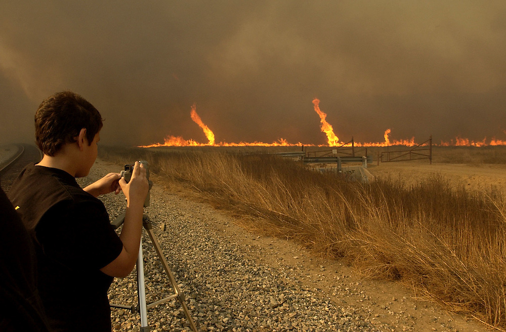 Austin Cabriales, 14, of Simi Valley video tapes the wildfire as high winds cause it to form small tornadoes in the brush across the street from the 12100 block of Poindexter Avenue in Moorpark on Sunday afternoon.