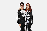 Portrait of happy couple in skeleton costume against gray background