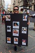 New York, NY - 25 June 2017. New York City Heritage of Pride March filled Fifth Avenue for hours with groups from the LGBT community and it's supporters. A man with a board with names and photos of ten people killed in the Pulse nightclub in June 2016.