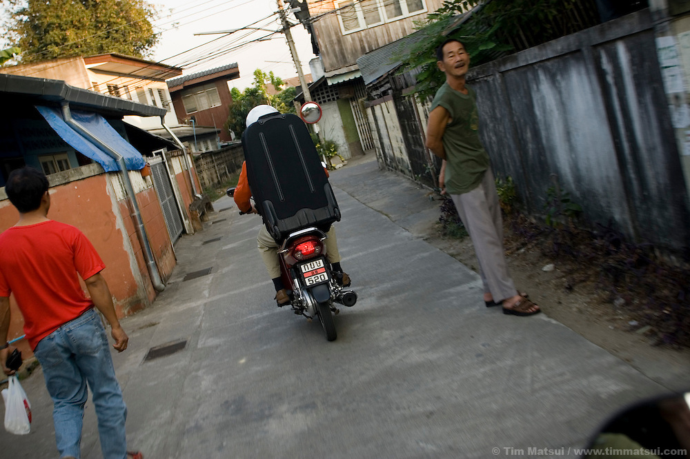 Driving a motorcycle with heavy luggage through the streets of Chiang Mai, Thailand.