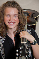 Portrait of smiling young musician with guitar over shoulder