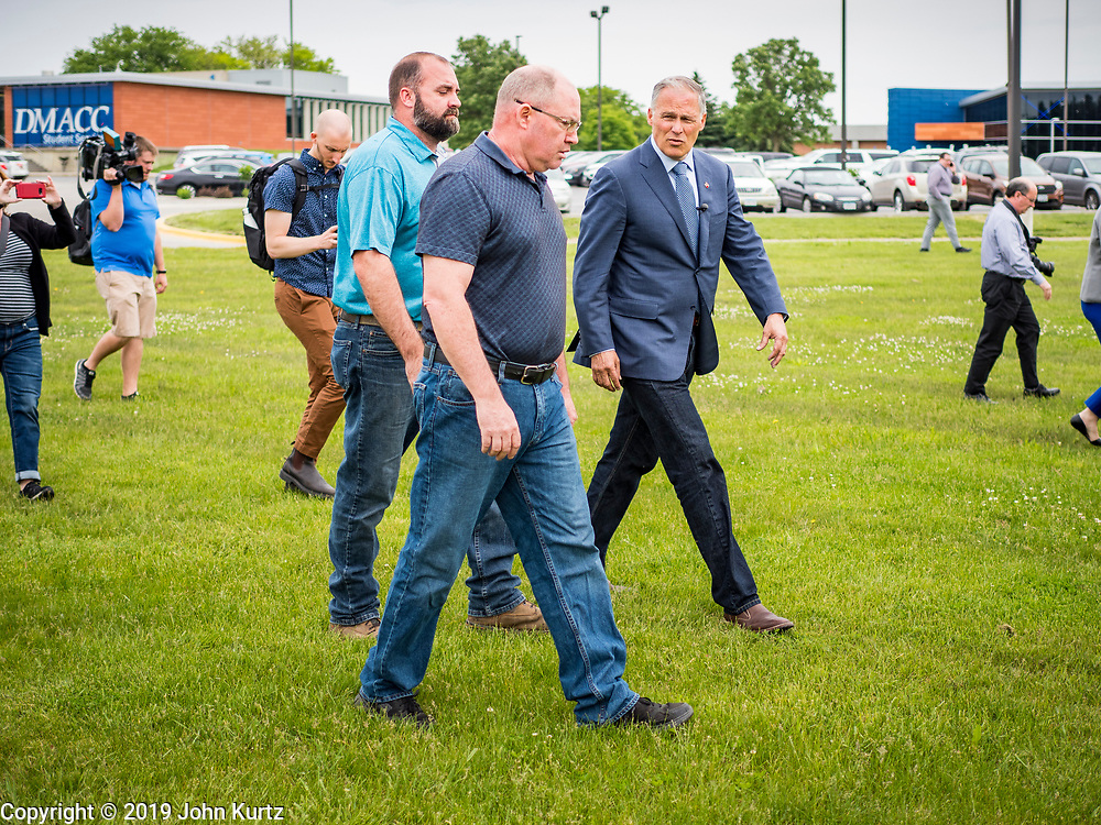 03 JUNE 2019 - ANKENY, IOWA: Governor JAY INSLEE, (D-WA), right, and members of the DMACC faculty walk out to a wind turbine during a tour at DMACC Monday. Governor Inslee is running to be the Democratic candidate for the US Presidency in 2020, He has made climate change a central point of his campaign and he toured a wind turbine program at the Des Moines Area Community College (DMACC) in Ankeny. Iowa generates more than 35% of its electrical needs through wind power. Iowa traditionally hosts the the first election event of the presidential election cycle. The Iowa Caucuses will be on Feb. 3, 2020.                       PHOTO BY JACK KURTZ
