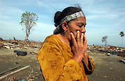 Banda Aceh, Northern Sumatra, Indonesia.<br />Site of the worst destruction of the Boxing day 2004 earthquake and subsequent tsunami.<br />Ms Wardiah returns to the site of her house in Desa Kajho an outer suburb of Banda Aceh. Her house was destroyed, and her son is missing, feared dead.